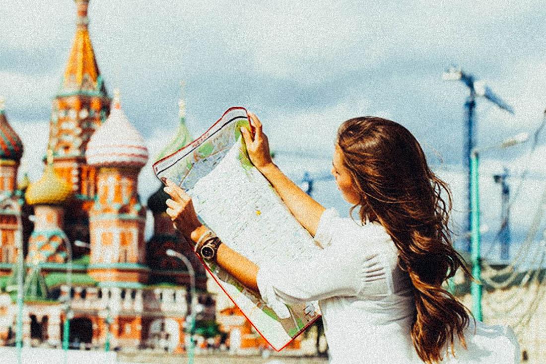 девушка смотрит туристическую карту на фоне кремля